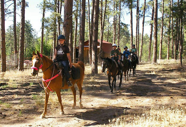 Campers at Friendly Pines Camp enjoy a horseback ride on trails through Prescott National Forest.