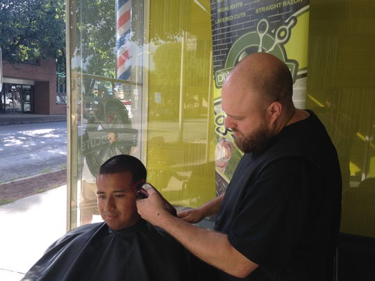 Josh Myers cuts Victor Martinez's hair outside of Diversified Cuts Barbershop in Hanover after the power went out Monday afternoon.