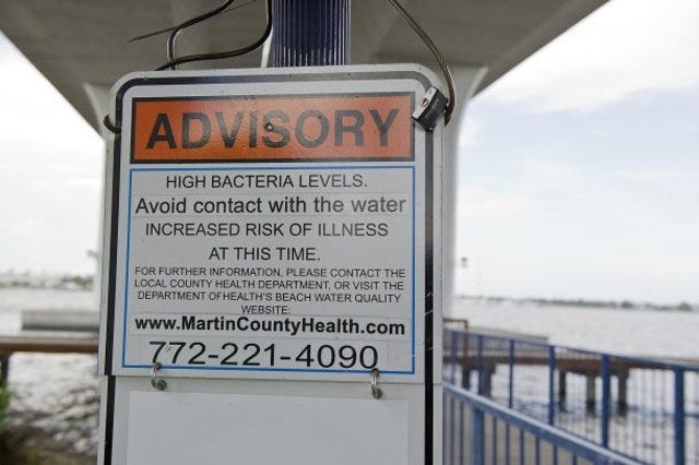 An advisory warning of high bacteria levels in the St. Lucie River is seen in July 2013 at the Roosevelt Bridge in Stuart.