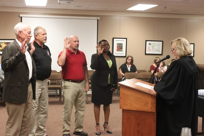 Juvenile Court Judge Christy Little swears Jim Campbell, Wayne Arnold, Kevin Alexander and Janice Hampton into the Jackson-Madison County School Board.