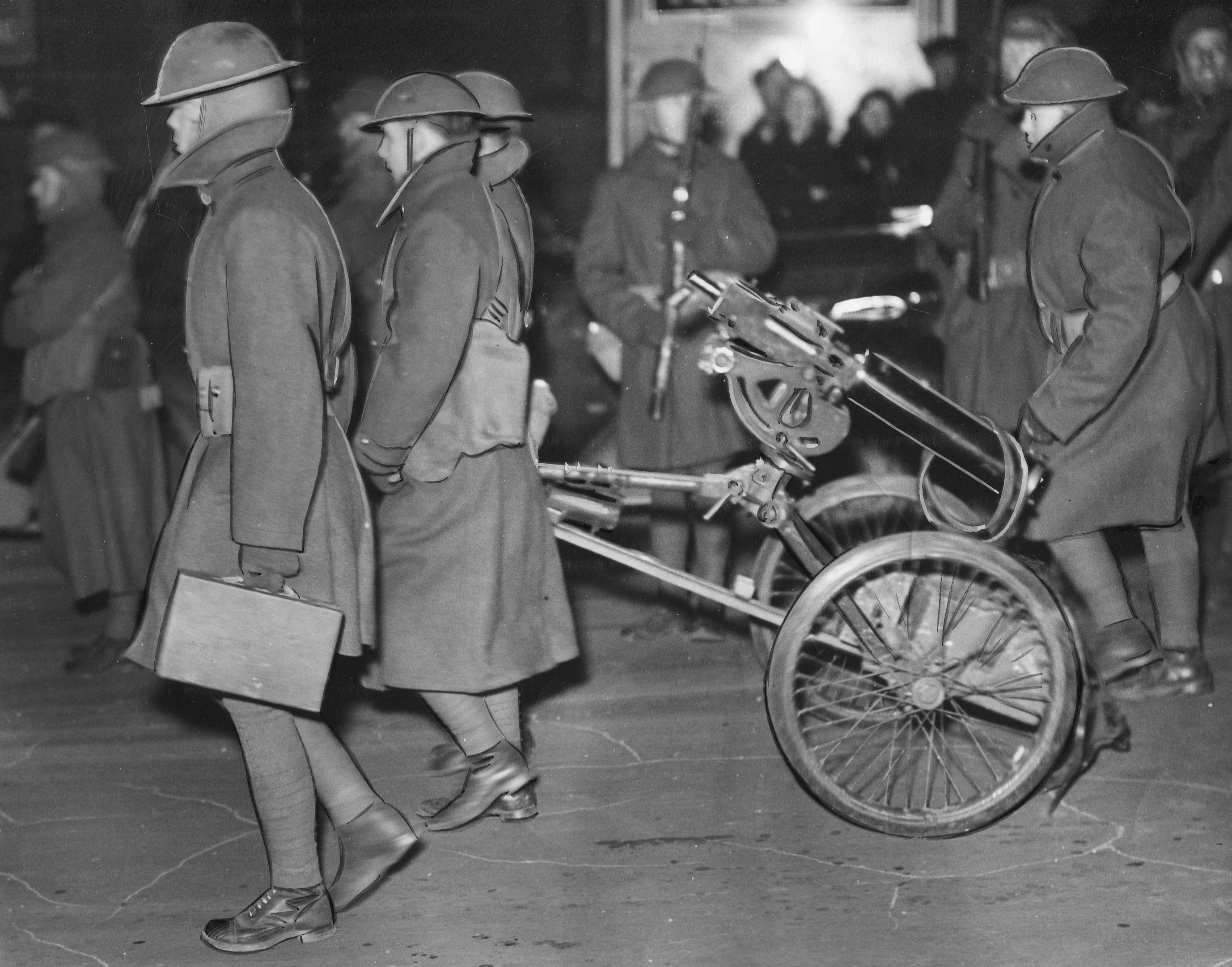 Michigan National Guardmen wheel machine guns during