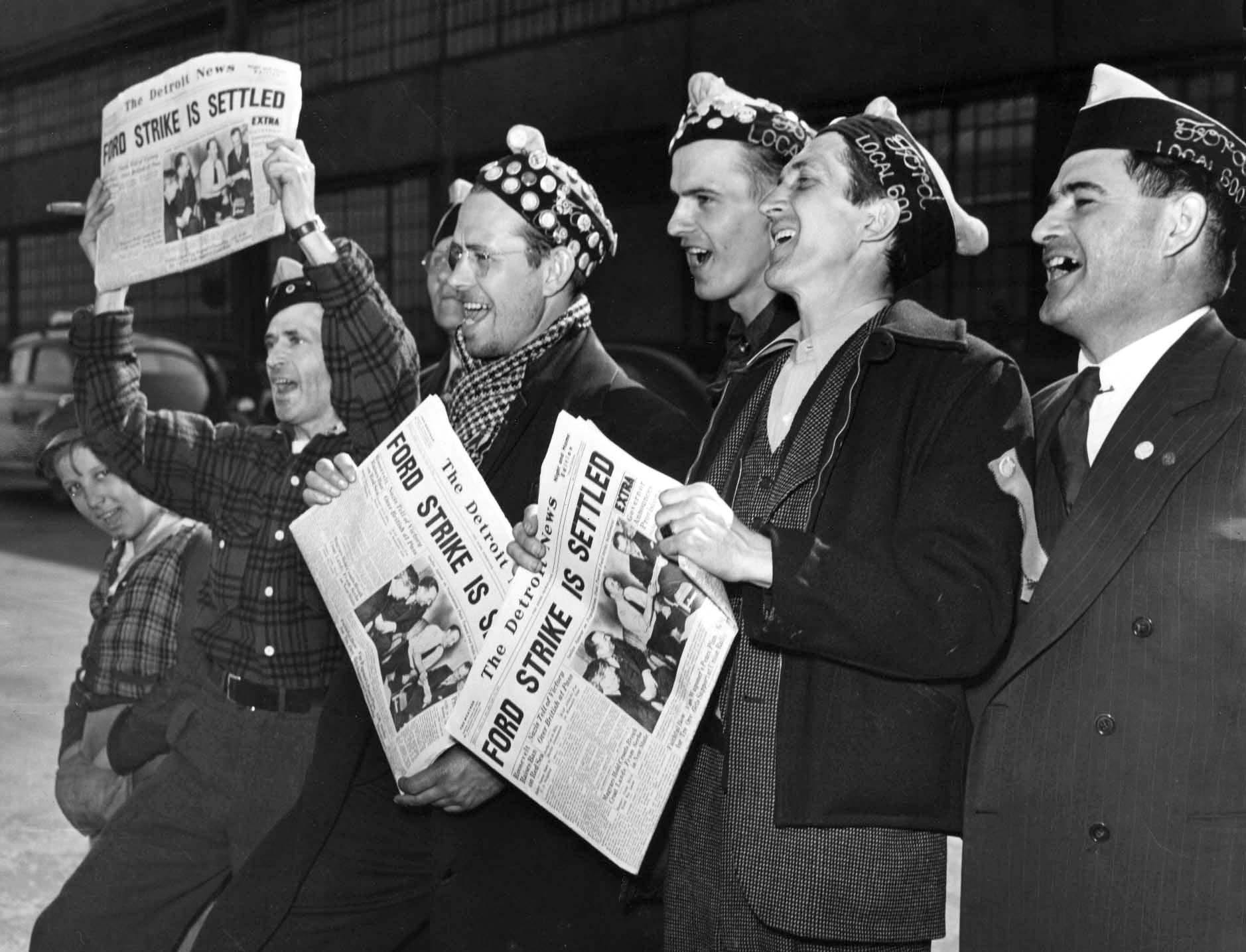 Strikers hold up The Detroit News announcing the end