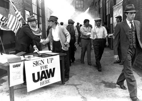A UAW organizer signs up members. Undated photo.