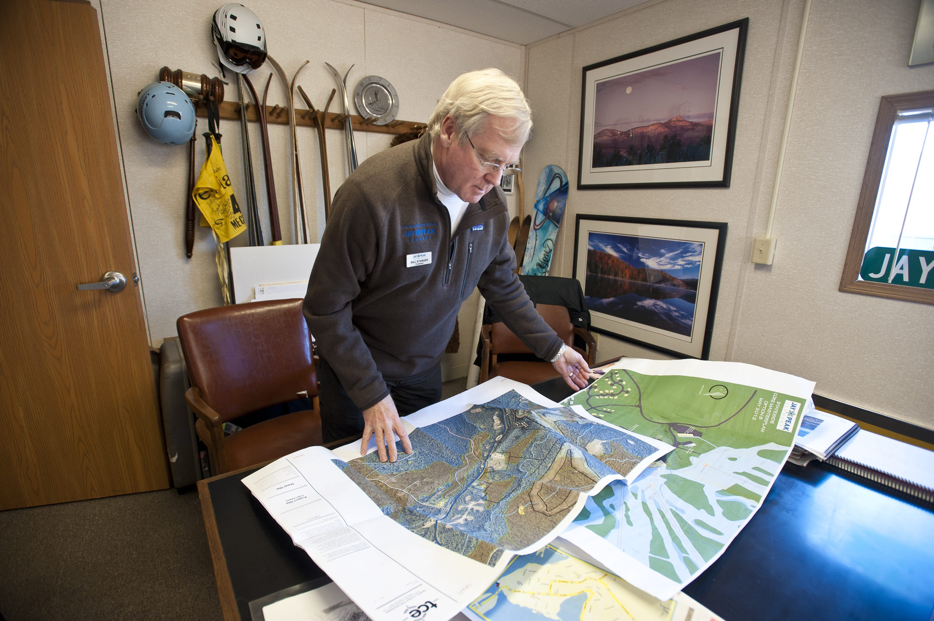 Jay Peak Resort President Bill Stenger looks at proposed development plans and maps in his office on Monday, November 19, 2012.