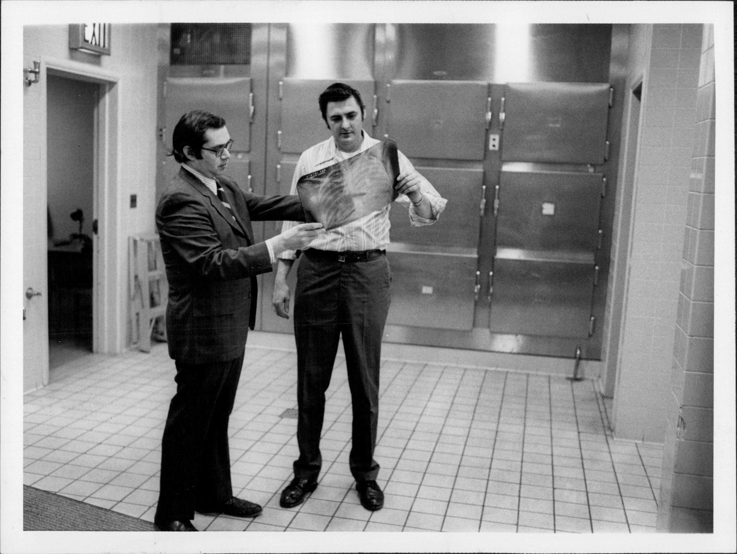 Dr. John Edland, left, and Ed Riley with an X-ray image in Monroe County Medical Examiner's Office in 1972.