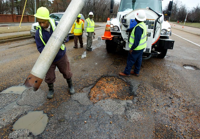 Crews remove water from the street to make way for asphalt after freezing weather caused large potholes to open up.