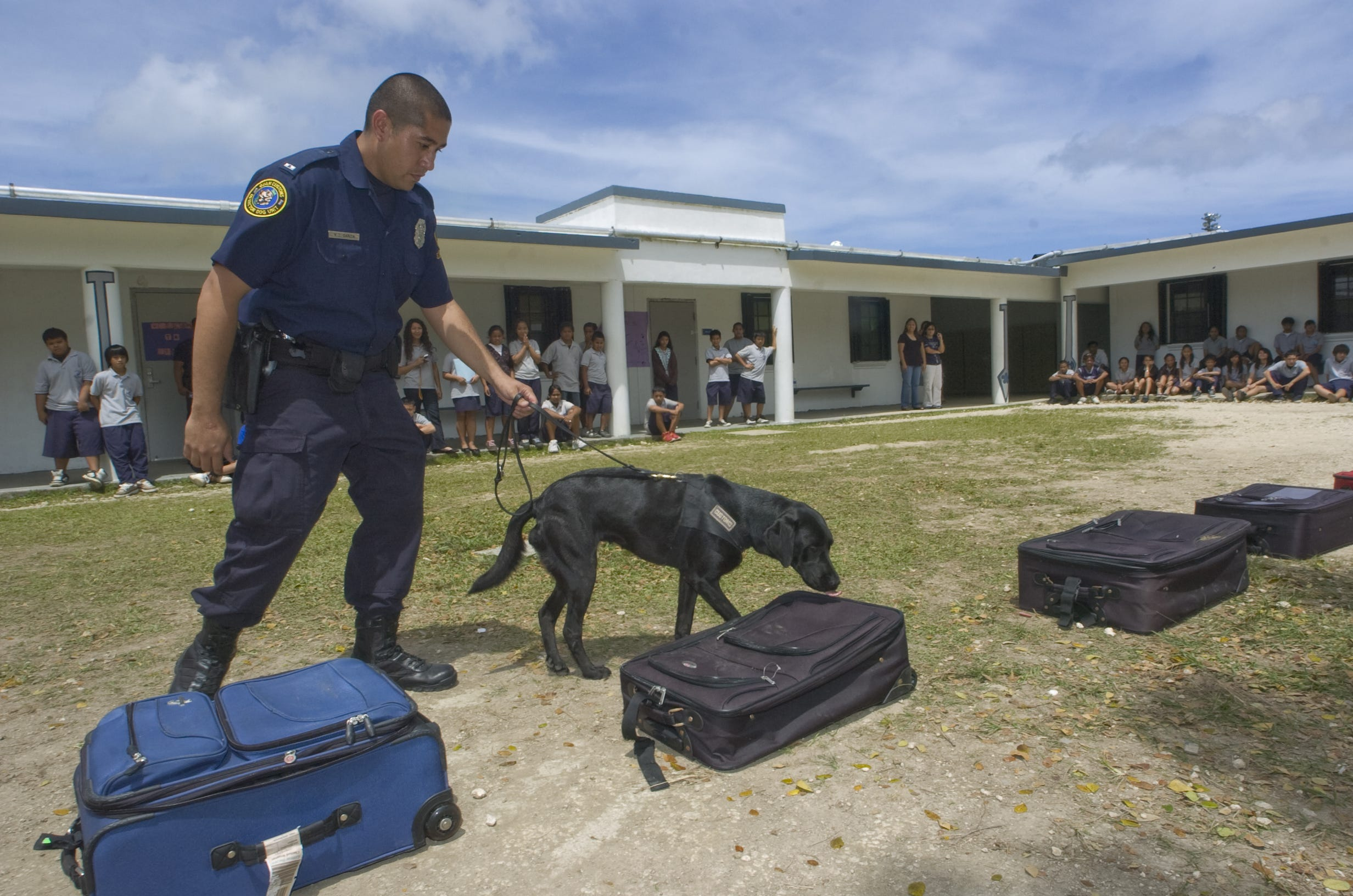 In this file photo, Guam Customs and Quarantine Officer Mark Garcia and drug detector dog Toya demonstrate how they detect drugs hidden in luggage at Jose Rios Middle School. Sen. Frank Aguon Jr. said he introduced a bill to reinstate hazard pay for customs employees.