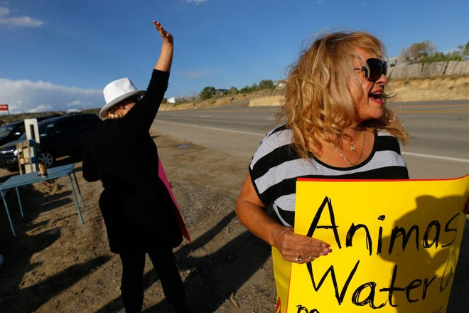 Heather Lamprecht, left, and Stella Padilla yell at passing cars during a protest against AV Water Co. at County Road 350 and 390 in Crouch Mesa in this September 2016 file photo.