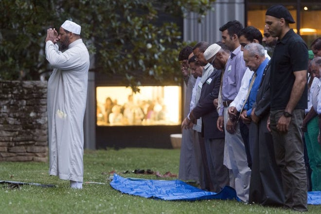 SAUL YOUNG/NEWS SENTINEL Imam Rafiq Mahdi leads prayer before breaking fast during the Muslim Community of Knoxville's sixth annual Ramadan Iftar at the Knoxville Botanical Gardens last June.