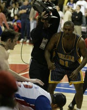 Indiana Pacers' Ron Artest knocks down a fan with a punch after the fan came on the court near the end of the altercation in the last minute of a game against the Pistons at the Palace of Auburn Hills on Nov. 19, 2004.