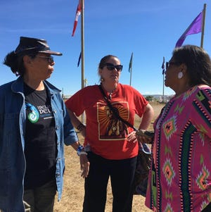 Beth Castle, center, stands with tribal elders Madonna Thunder Hawk, left, and Phyllis Young, who are instrumental in keeping the Sioux Nation camp at Standing Rock running.