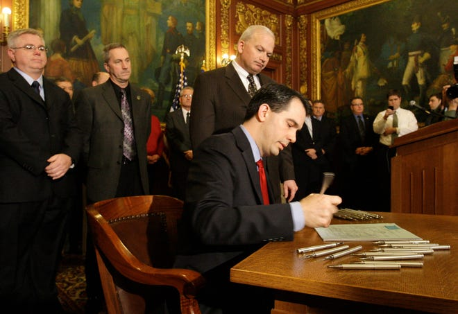 Gov. Scott Walker is surrounded by Republican Assembly, Senate and Cabinet members as he signs his amended Budget Repair Bill in the governor's conference room at the Wisconsin State Capitol on March 11, 2011. The bill enacted Act 10.