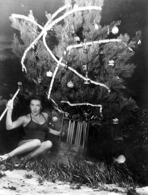 Mary Dwight displays croquet set gift she has just found under the underwater Christmas tree. 1948