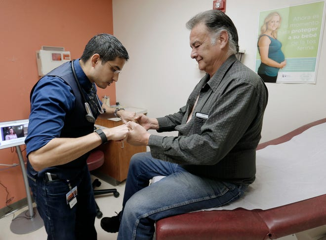 Centro San Vicente nurse practitioner Joshua Romero gives uninsured El Pasoan Robert Smalley, 56, his first physical in almost 40 years at the lower valley clinic.