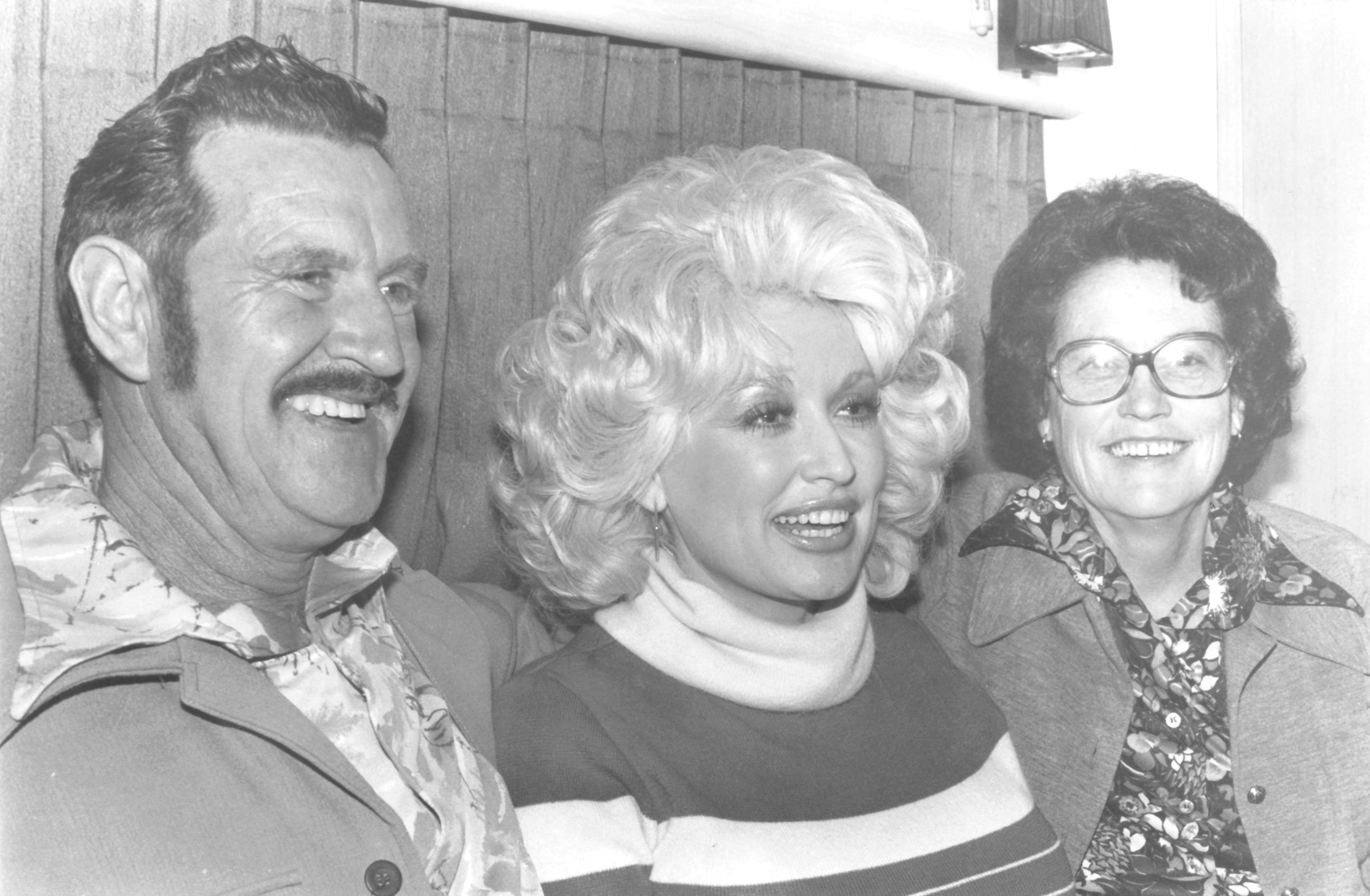 Dolly Parton, flanked by parents Lee and Avie Lee Parton in 1977, is one of 12 children.