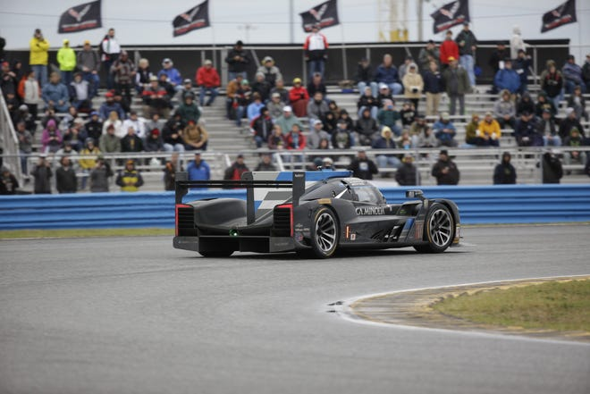 Jordan Taylor in a Cadillac Dpi drives through the east horseshoe turn in the IMSA 24-hour auto race at Daytona International Speedway.