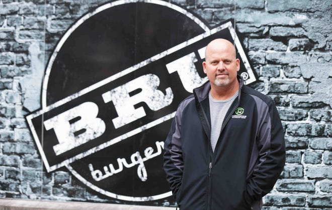 Mike Cunningham in front of Bru Burger Bar, one of Mass Ave.'s most-recognized brands and among five restaurants Cunningham owns on Mass  Ave. as part of his Cunningham Restaurant Group.
