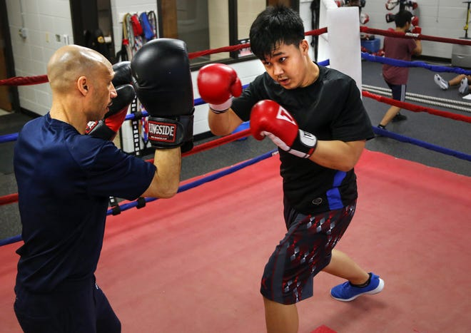Des Moines Senior Police Officer John Saunders works with Eh Htee Kaw, 12, at the Des Moines Police Boxing Club on Thursday, Jan. 26, 2017.