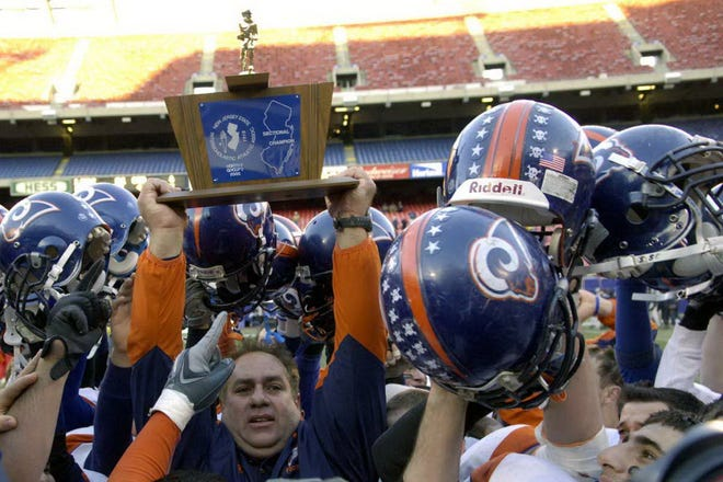 From 2005: Lodi head football coach Pat Tirico holds up the sectional championship trophy at Giants Stadium.