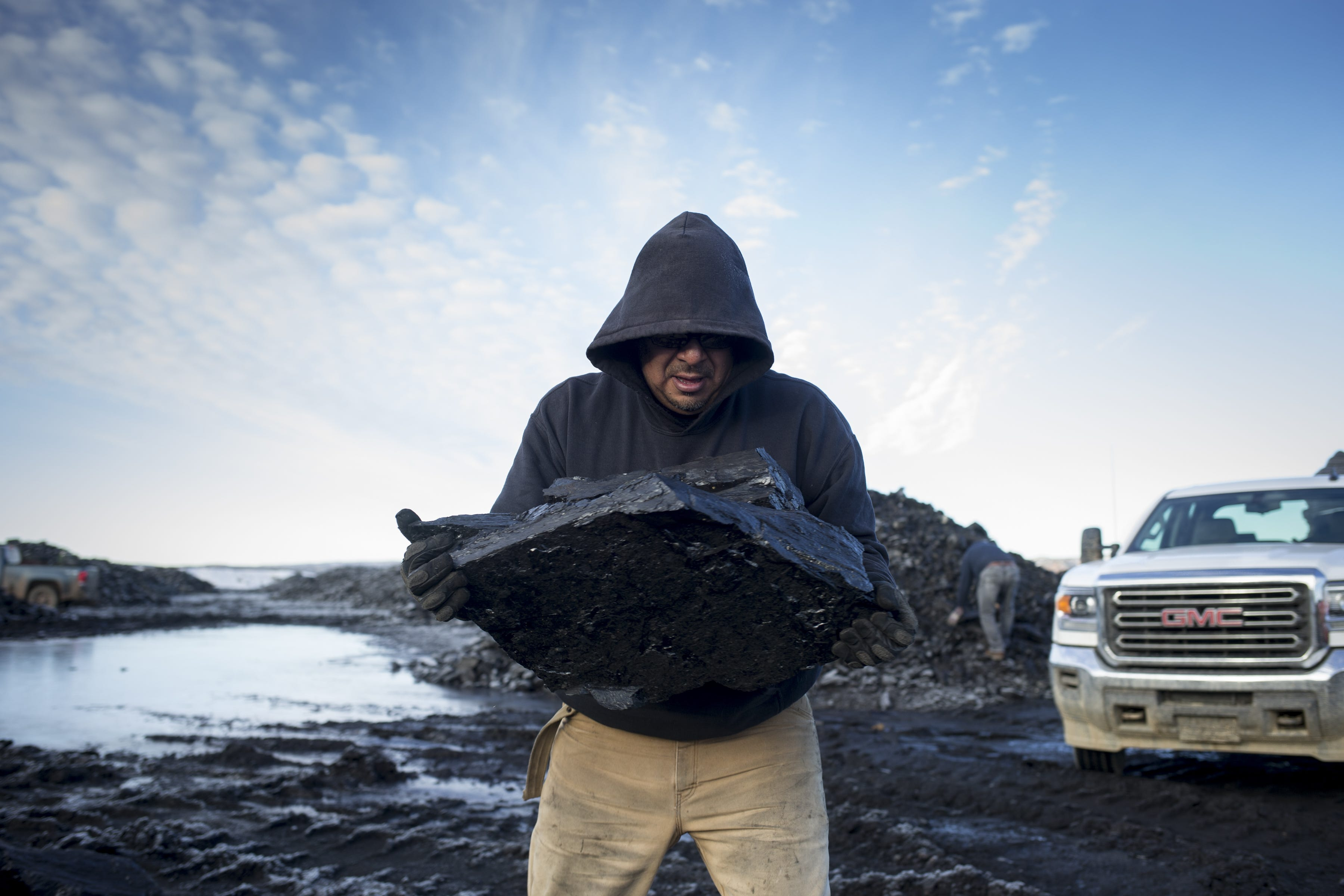 Al Lomayestewa carries a large piece of coal back to