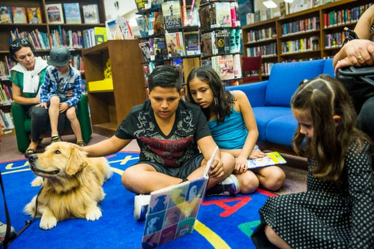 Ranferi Cifuentes, 11, and sister Kaelyn, 9, of Naples read to D.B., a service dog from PAWS Assistant Dogs, while reading during Pups 'n' Books at East Naples Branch Library on Thursday, March 23, 2017.