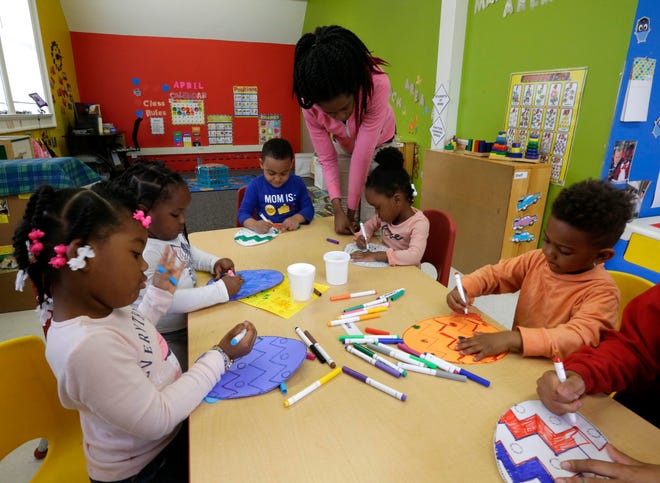 Monica Gist, teaching assistant at Kid-Tastic Child Care, helps pre-school children with their Easter projects.