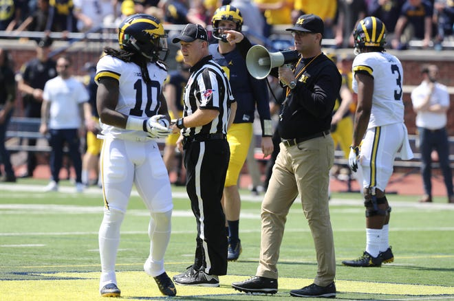 Michigan head coach Jim Harbaugh talks with linebacker Devin Bush during the spring game Saturday, April 15, 2017 at Michigan Stadium in Ann Arbor.