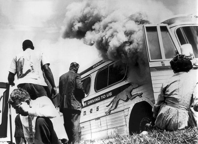 Freedom Riders on a Greyhound bus sponsored by the Congress of Racial Equality (CORE) sit on the ground outside the bus after it was set afire by a group of whites who met the group on arrival at Anniston, Ala., on May 14, 1961.