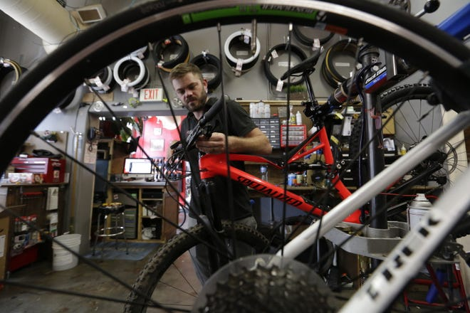 Ben Rennert, owner of Winnebago Bicycle, works on a bicycle, Wednesday, May 3, 2017, in Oshkosh. Rennert will be one of the speakers at A Night of Great Inspiration at the University of Wisconsin-Oshkosh, where he will share his experience over dinner with a group of people.