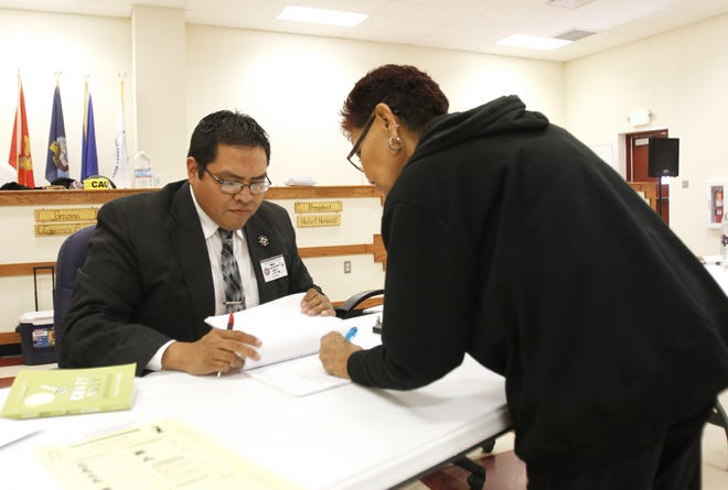 Poll worker Jamie Joe helps voter Irene Mason receive her ballot during the Nov. 4, 2014, general election at the Upper Fruitland Chapter house in Upper Fruitland.