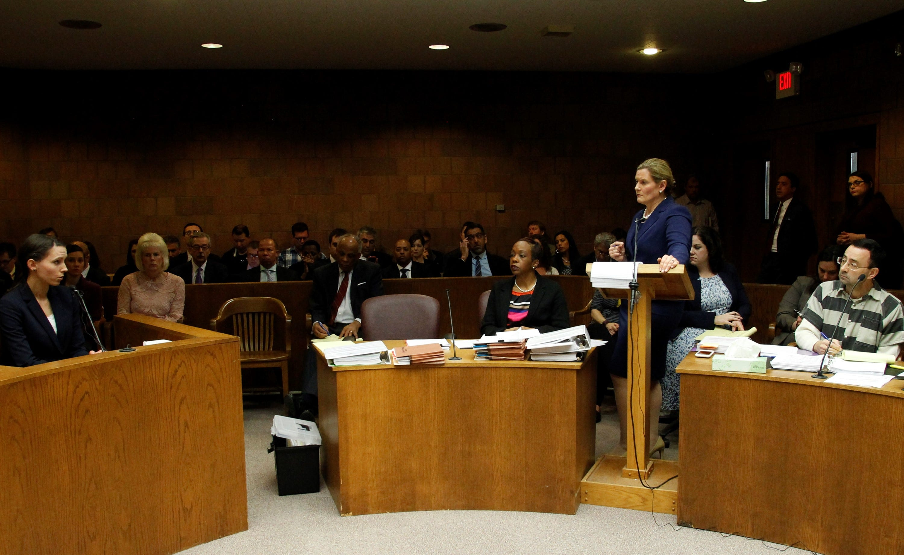 Rachael Denhollander answers questions from Assistant Attorney General Angela Povilaitis during a preliminary hearing for Larry Nassar in 55th District Court in Mason, Michigan on May 12, 2017. Nassar is seated just behind Povilaitis..