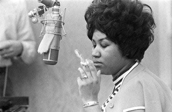 MUSCLE SHOALS, AL - JANUARY 9: Singer Aretha Franklin smokes as cigarette as she works in the studio by a microphone at Muscle Shoals Studios on January 9, 1969 in Muscle Shoals, Alabama. (Photo by Michael Ochs Archives/Getty Images)