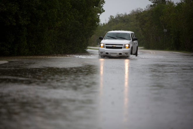An SUV drives through flooding on Goodland Road in Goodland on June 6, 2016.