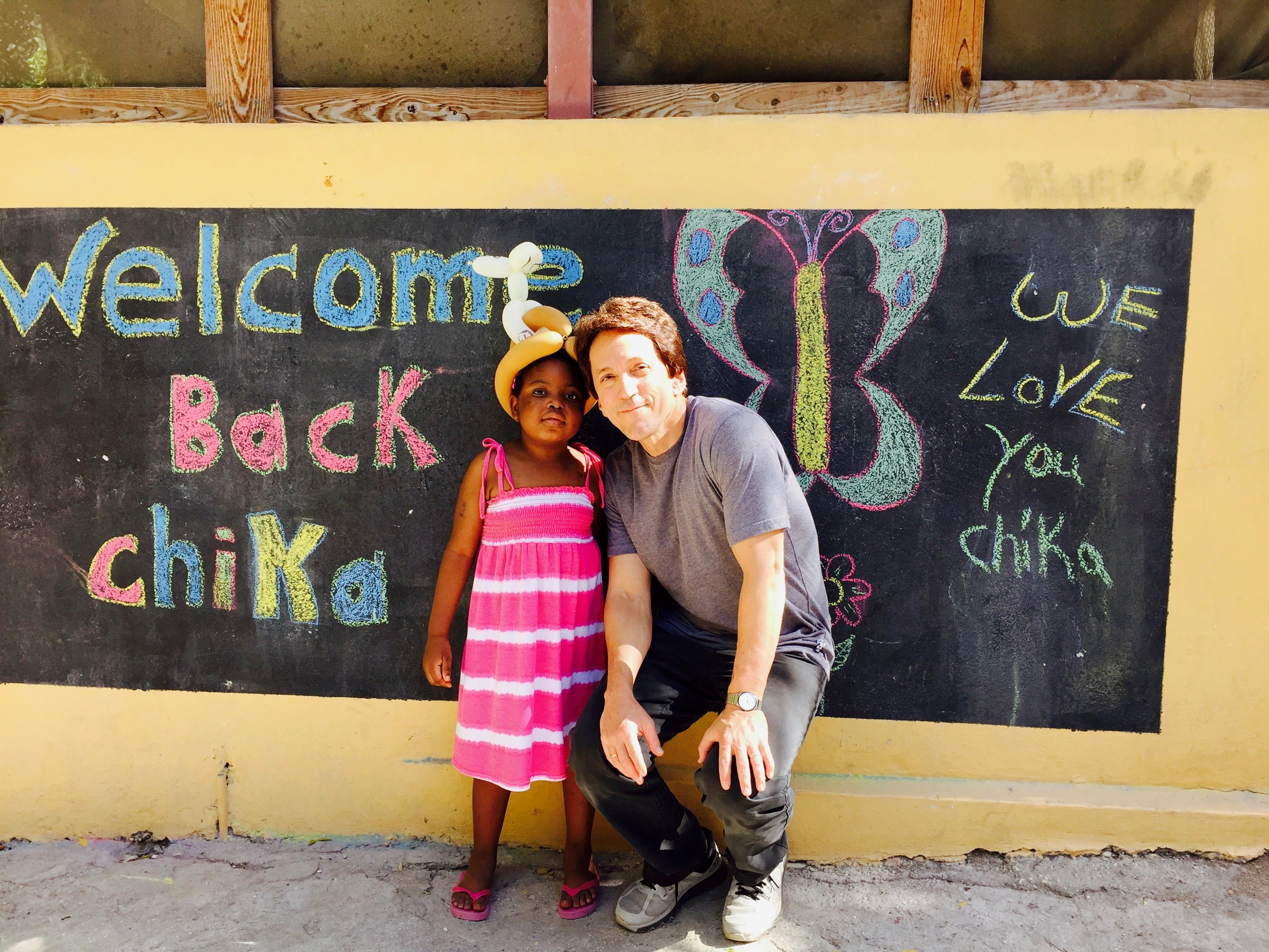 """For the first time since leaving for treatment, Chika returned to Haiti in December 2015. Her arrival was triumphant. The kids painted a welcome mural and when the SUV pulled up, chanted """"Chi-ka! Chi-ka!"""""""