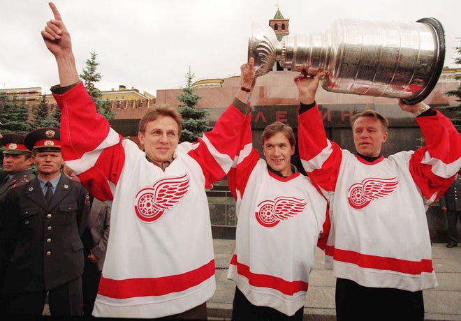 Detroit Red Wings' Viacheslav Fetisov, right, Vyacheslav Kozlov, center, and Igor Larionov hoist the Stanley Cup at Lenin's tomb in Moscow's Red Square on Aug. 17, 1997. The three brought the cup to Moscow for a tour of their hometown.