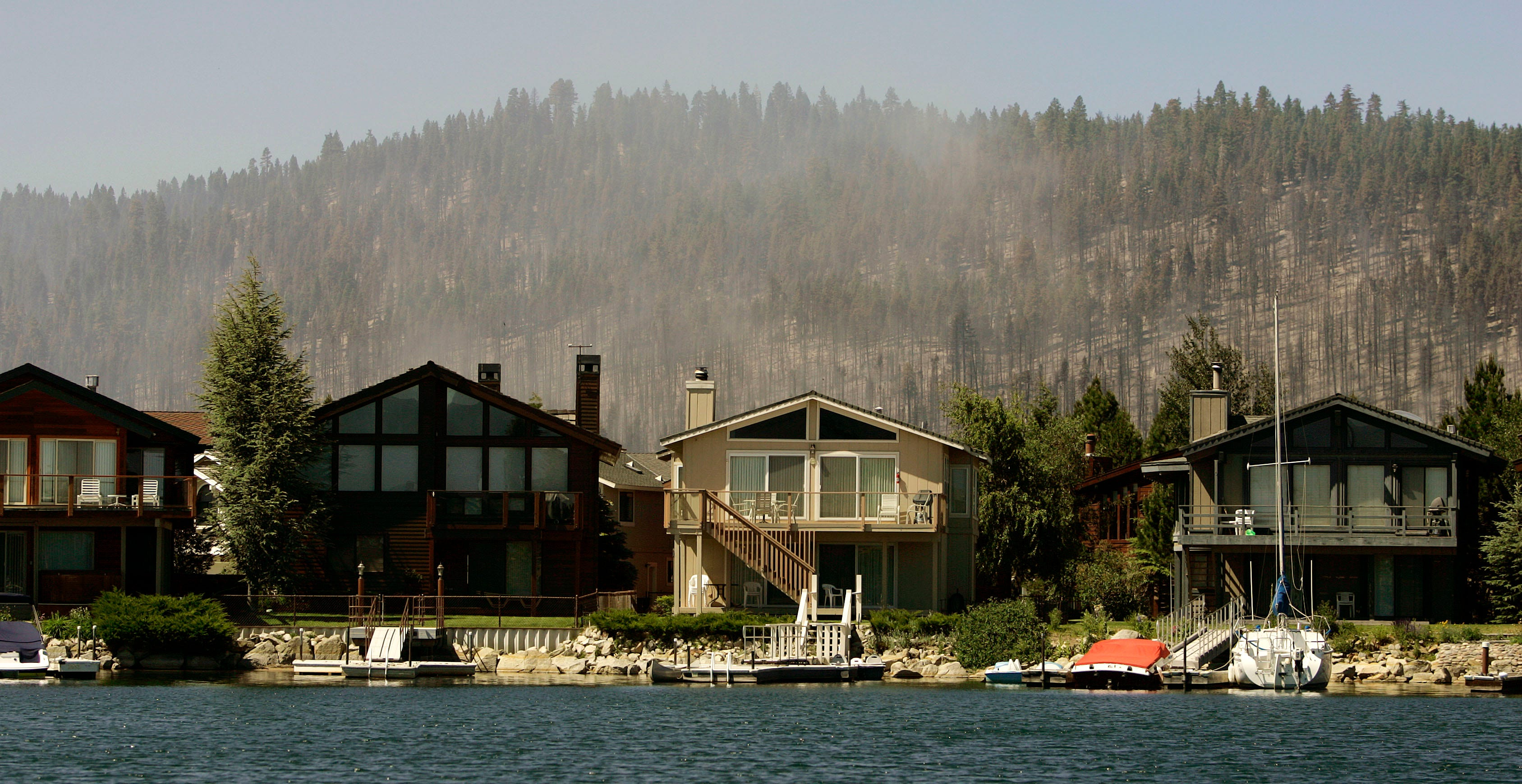 The Angora fire is seen on a hillside behind multi-million dollar lakefront homes of the Tahoe Keys area, which lie in the path of the fire, Thursday, June 28, 2007, in this view from Lake Tahoe, Calif. A break in the wind allowed firefighters to gain ground on a stubborn wildfire near Lake Tahoe as they prepared for more blustery conditions forecast for Thursday. (AP Photo/Ben Margot)