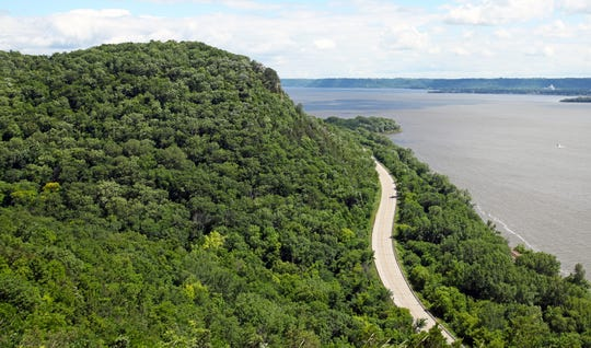 The Great River Road winds around Maiden Rock Bluff along Lake Pepin, a lake on the Mississippi River.