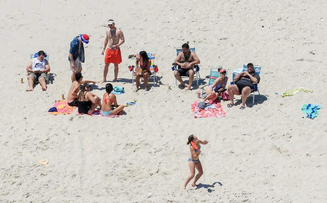 In this July 2 photo, Governor Christie, right, with his family and friends at the governor's summer house at Island Beach State Park.