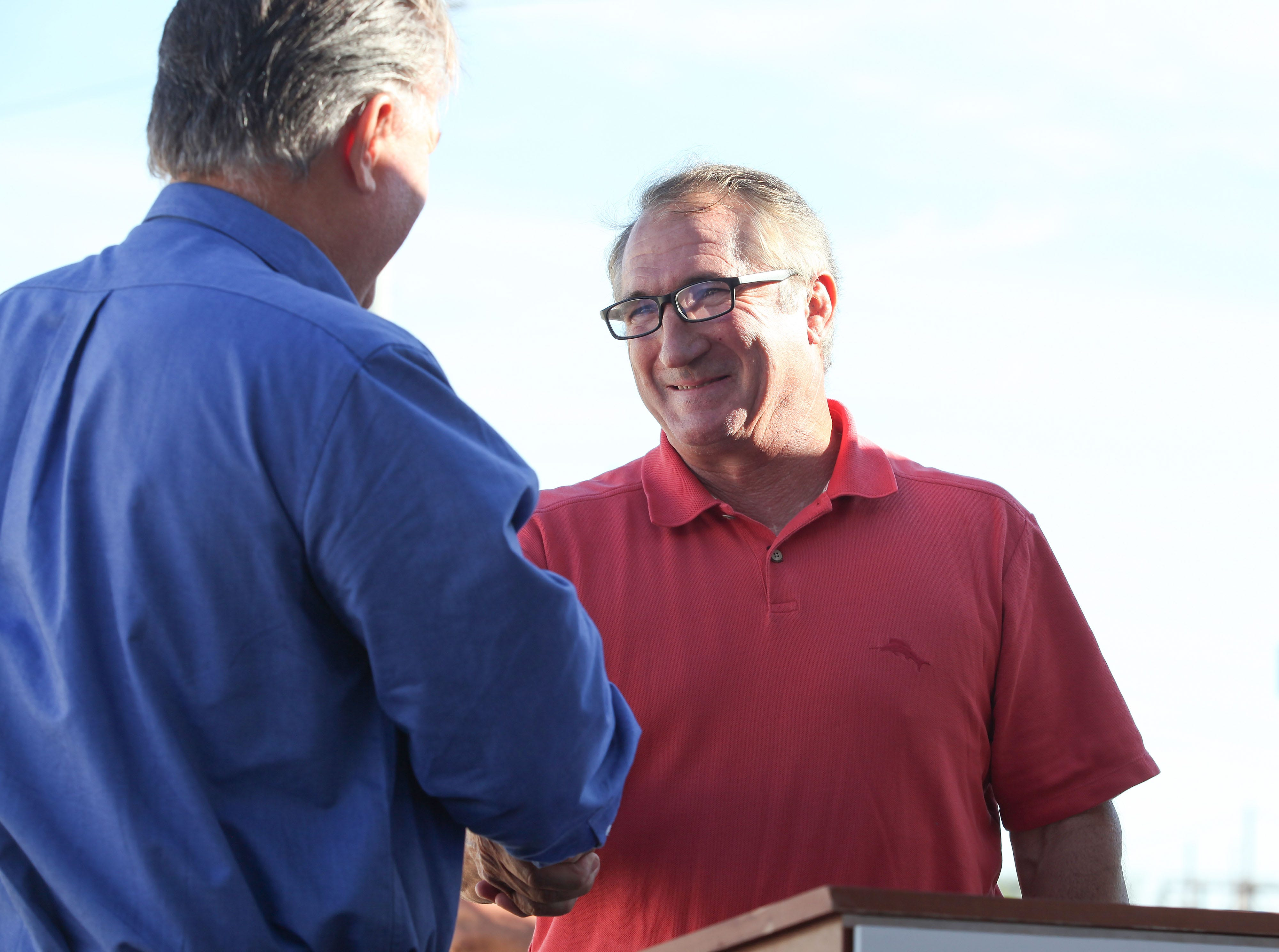 Then-Imperial Irrigation District board member Matt Dessert, left, greets his longtime friend Mike Abatti, a former IID board member and president of Coachella Energy Storage Partners, at an event celebrating the opening of IID's battery storage system in El Centro, California, on Oct. 26, 2016.