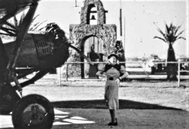 A woman poses by the Phoenix Sky Harbor airport fly-in chapel, circa 1930s.