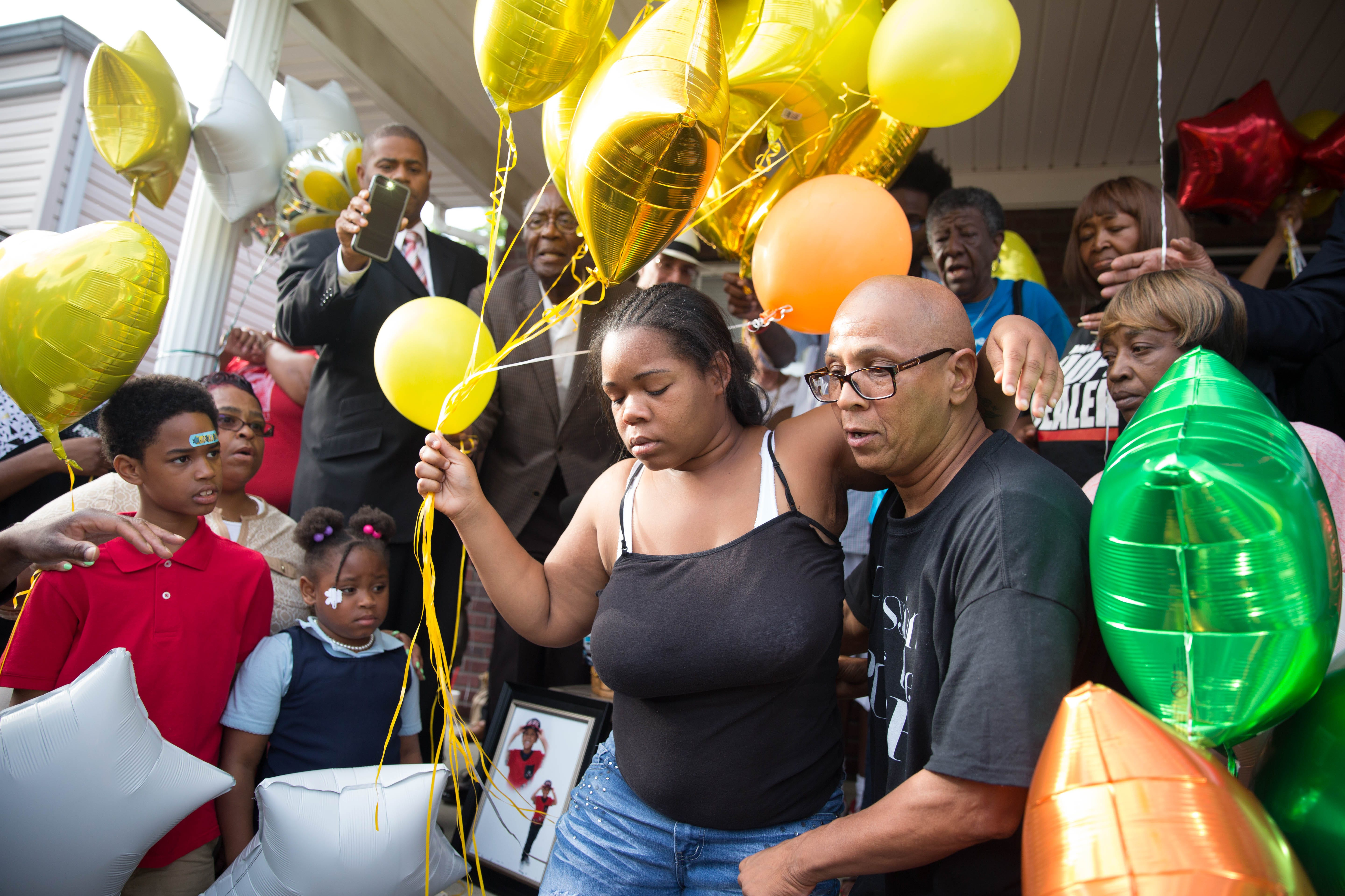 Christopher 2X, right, peace and justice activist and longtime family friend of Dequante Hobbs Jr. and his family, holds onto mother, Michesia Norment, as she releases the first balloons into the sky in memorial of her son. May 23, 2017.