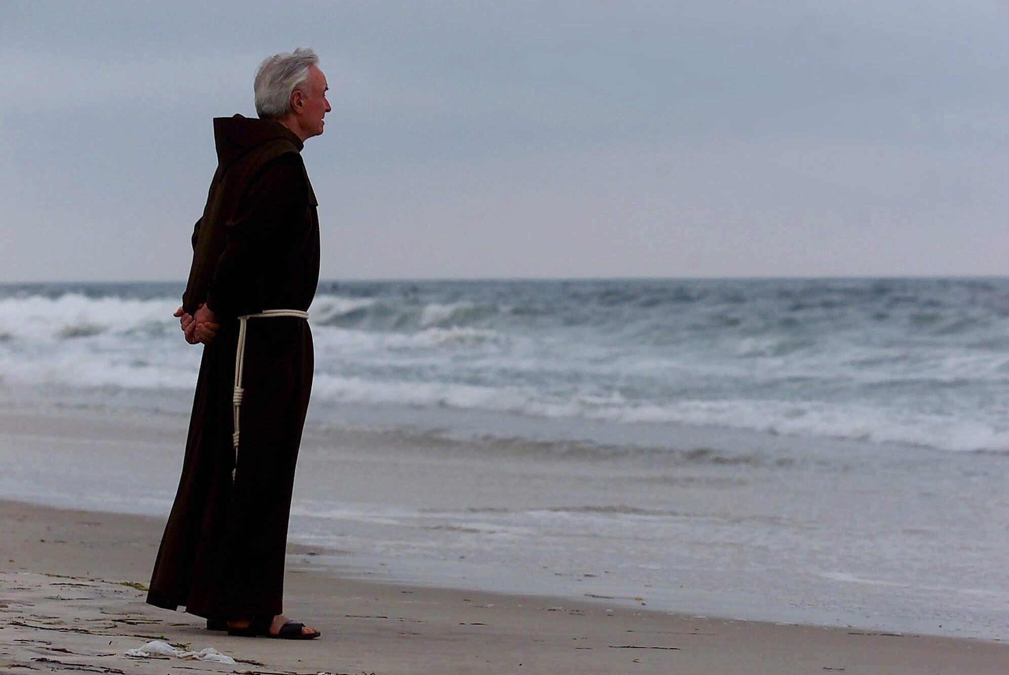 The Rev. Mychal Judge, who was the New York City Fire Department chaplain, stands on the Atlantic shore before a service where candles were lit for the victims of TWA Flight 800 on July 17, 2000, at Smith Point Park on Long Island.
