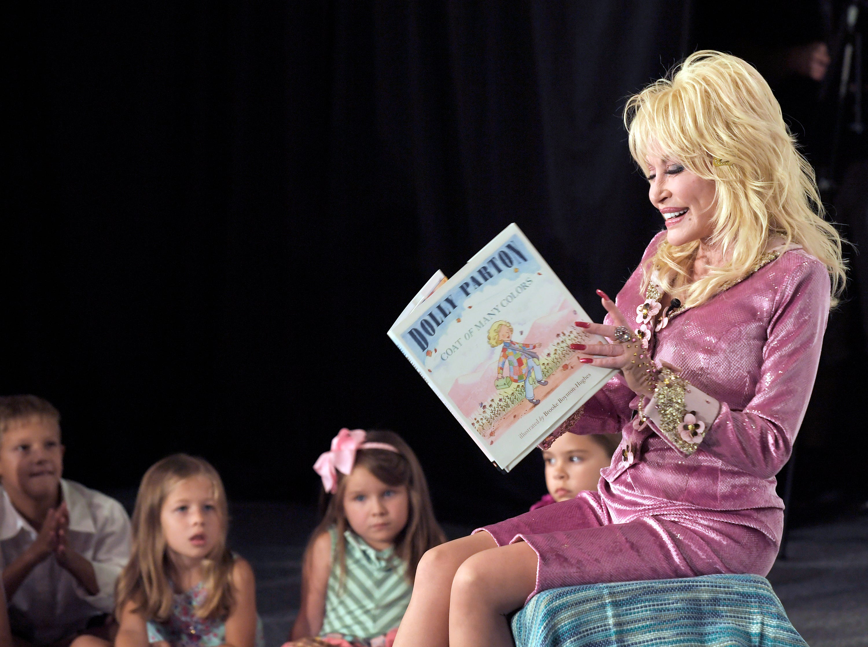 """Dolly Parton reads her children's book, """"Coat of Many Colors,"""" to a group of kids during an event announcing her first children's album, """"I Believe In You,"""" in 2017."""