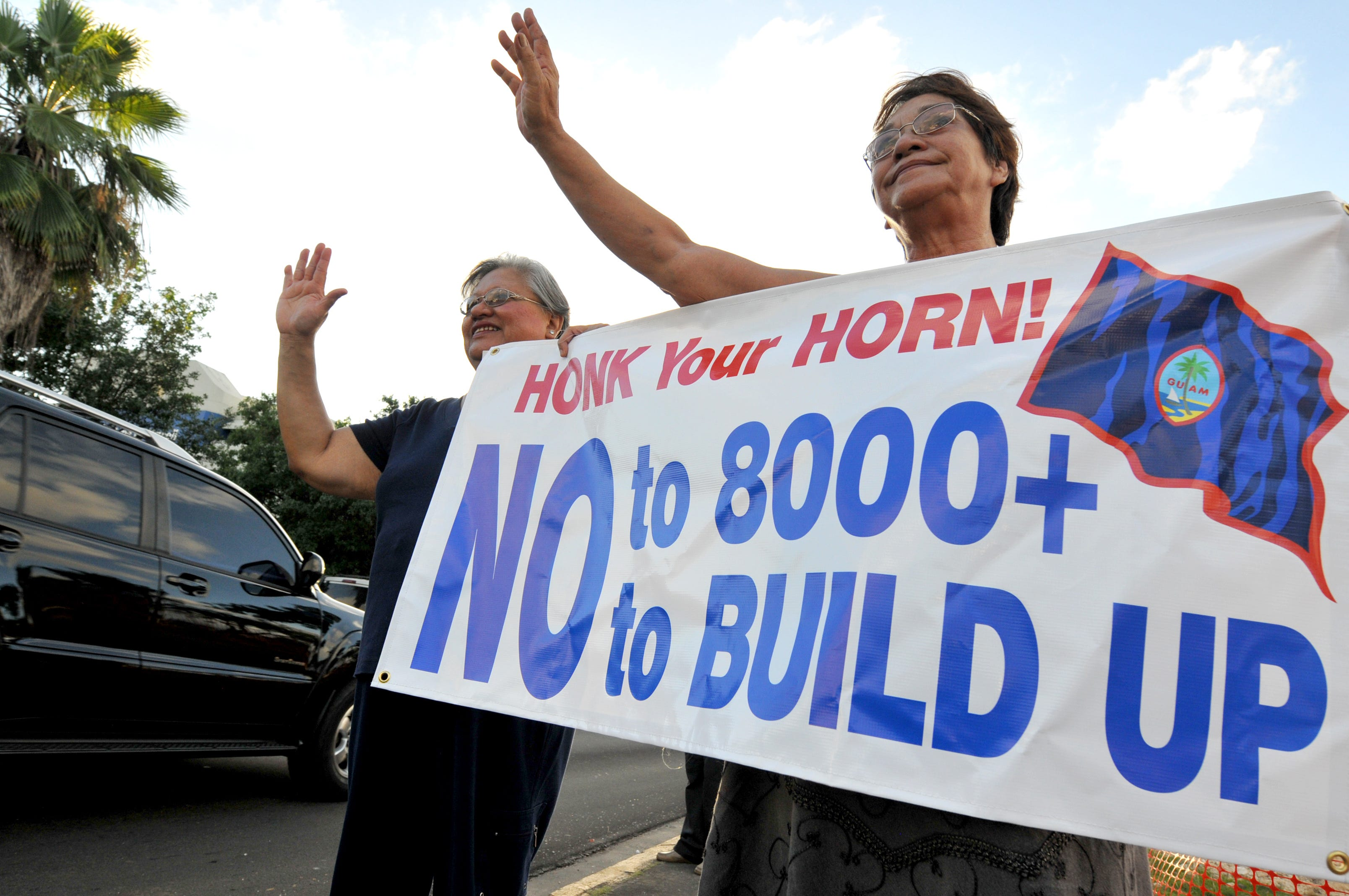 In this November 2009 file photo, Rose Taitano, left, and Margaret Taitano wave at motorists during a protest headed by the Taotaomona Native Rights Group, against the U.S. military buildup, at the Chief Quipuha Park in Hagatna.