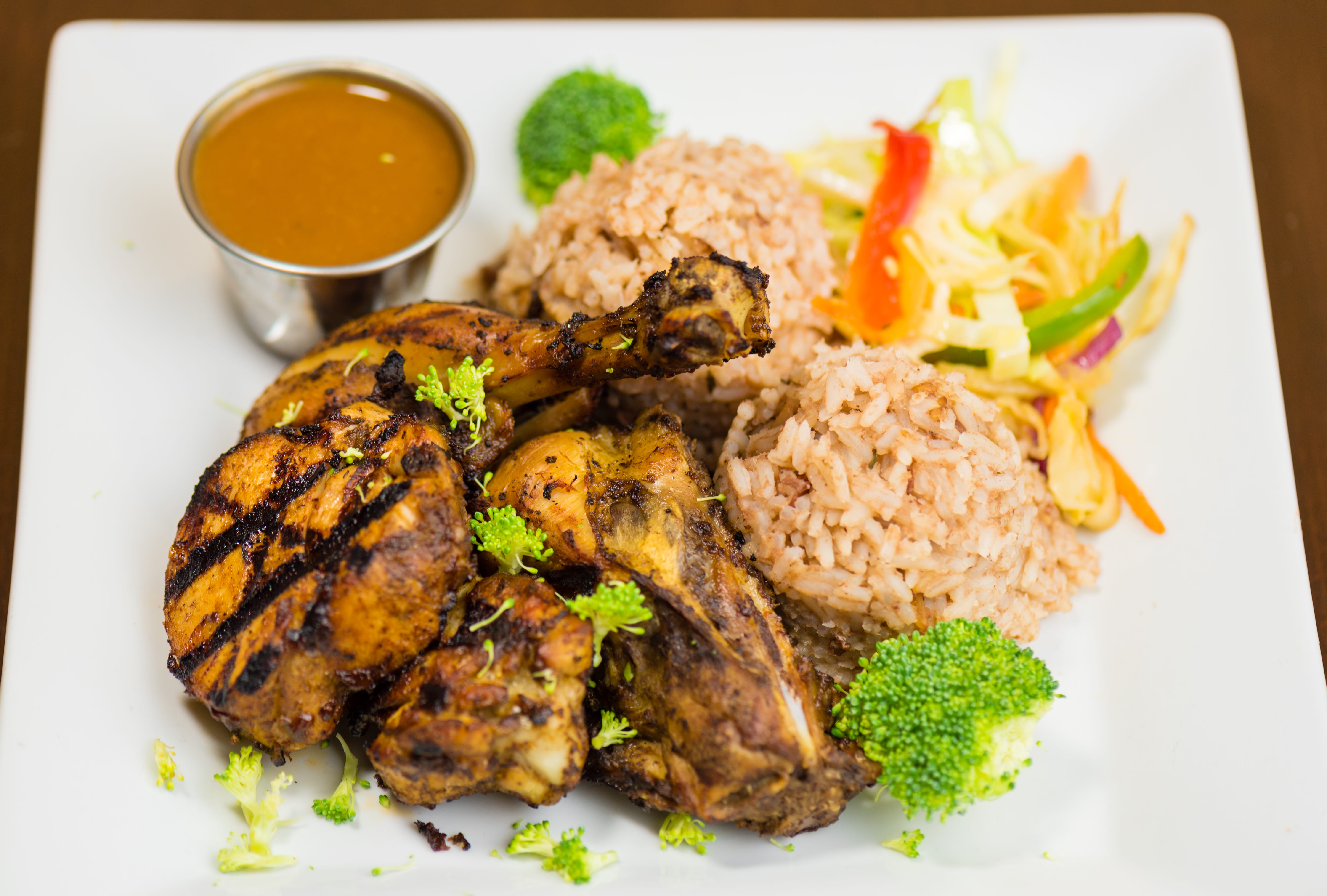 """Jerk chicken, a specialty of Jamaica, is dry rubbed or marinated in a hot spice mixture, and then slow-cooked. The word """"jerk"""" is said to come from charqui, a Spanish term of Quechua origin for dried meat — also the basis for the English word """"jerky.""""  This platter is from Simply Jerk in Monroe Township, New Jersey."""