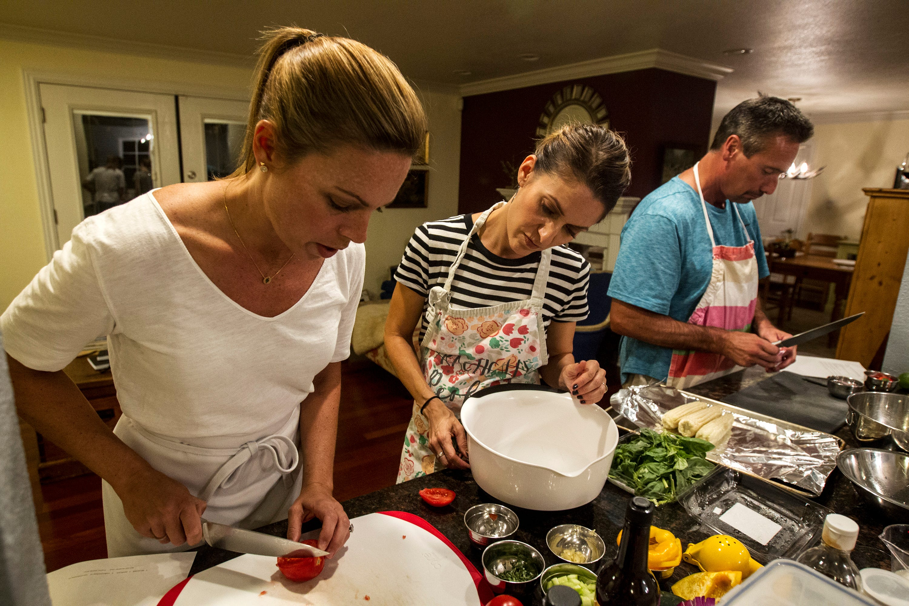 Maggie Norris, left, demonstrates basic knife skills for Michelle Wong while Michael Lopez preps ingredients during a private class at Whisked Away, a cooking school for amateur home chefs, on Sept. 12, 2017, in Phoenix. Norris has been teaching the classes from her home since 2009.