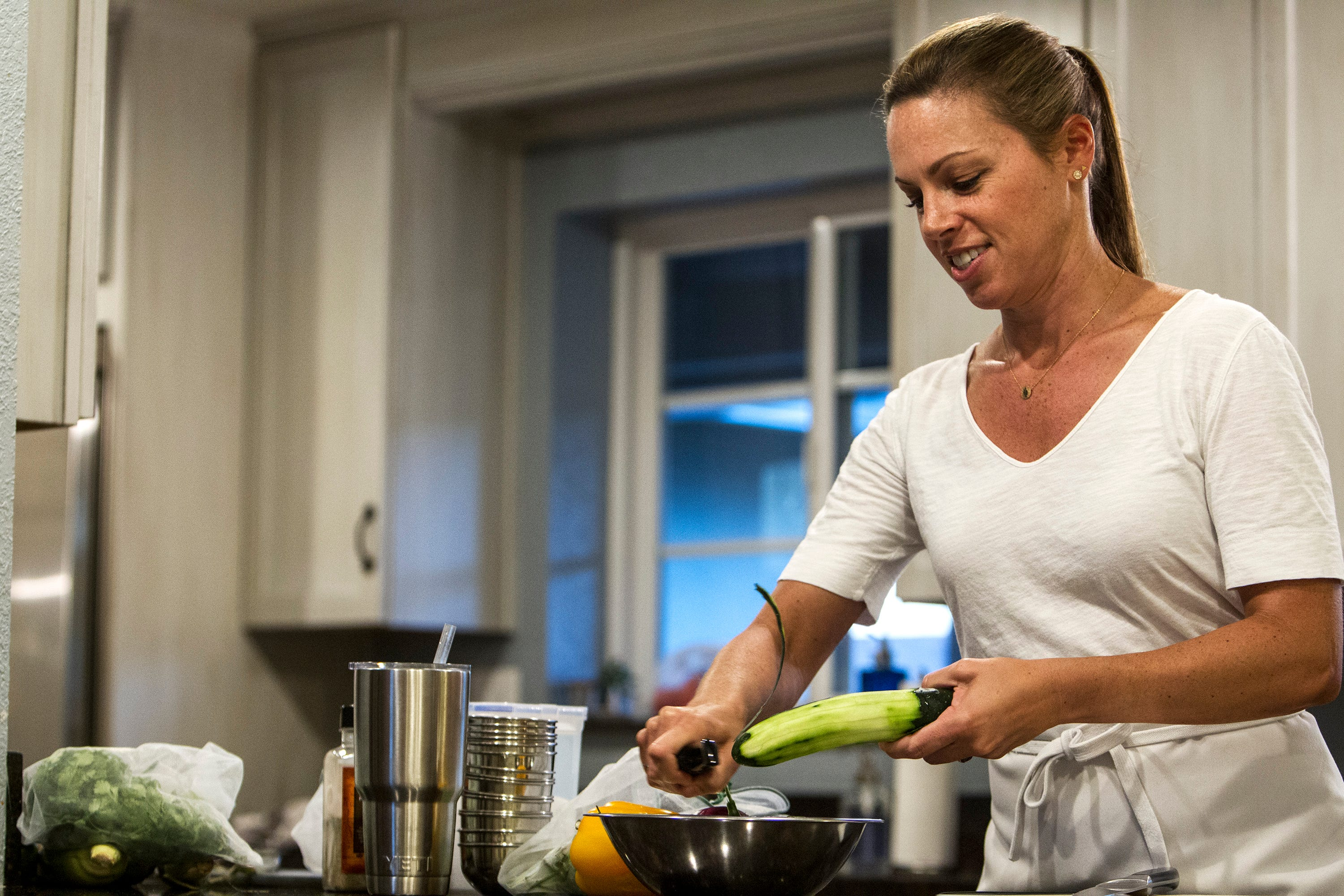 Maggie Norris peels skin off a cucumber during a private class at Whisked Away, a cooking school for home chefs, on Sept. 12, 2017, in Phoenix. Norris has been teaching the classes from her home since 2009.