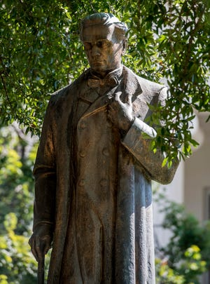 The statue of Dr. James Marion Sims sits in the shade of an old oak tree on the grounds of the state capitol building in Montgomery.
