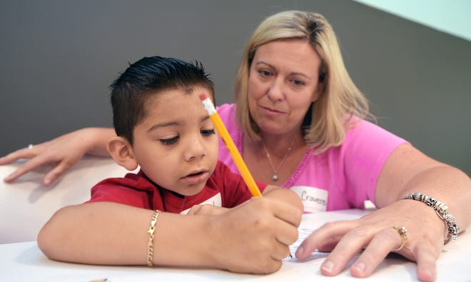 Franklin Special School District teacher Danette Cravens helps Alex Martinez, 5, with writing his name during the three-day 'Get Ready for Kindergarten' class at the Franklin Estates mobile home community.