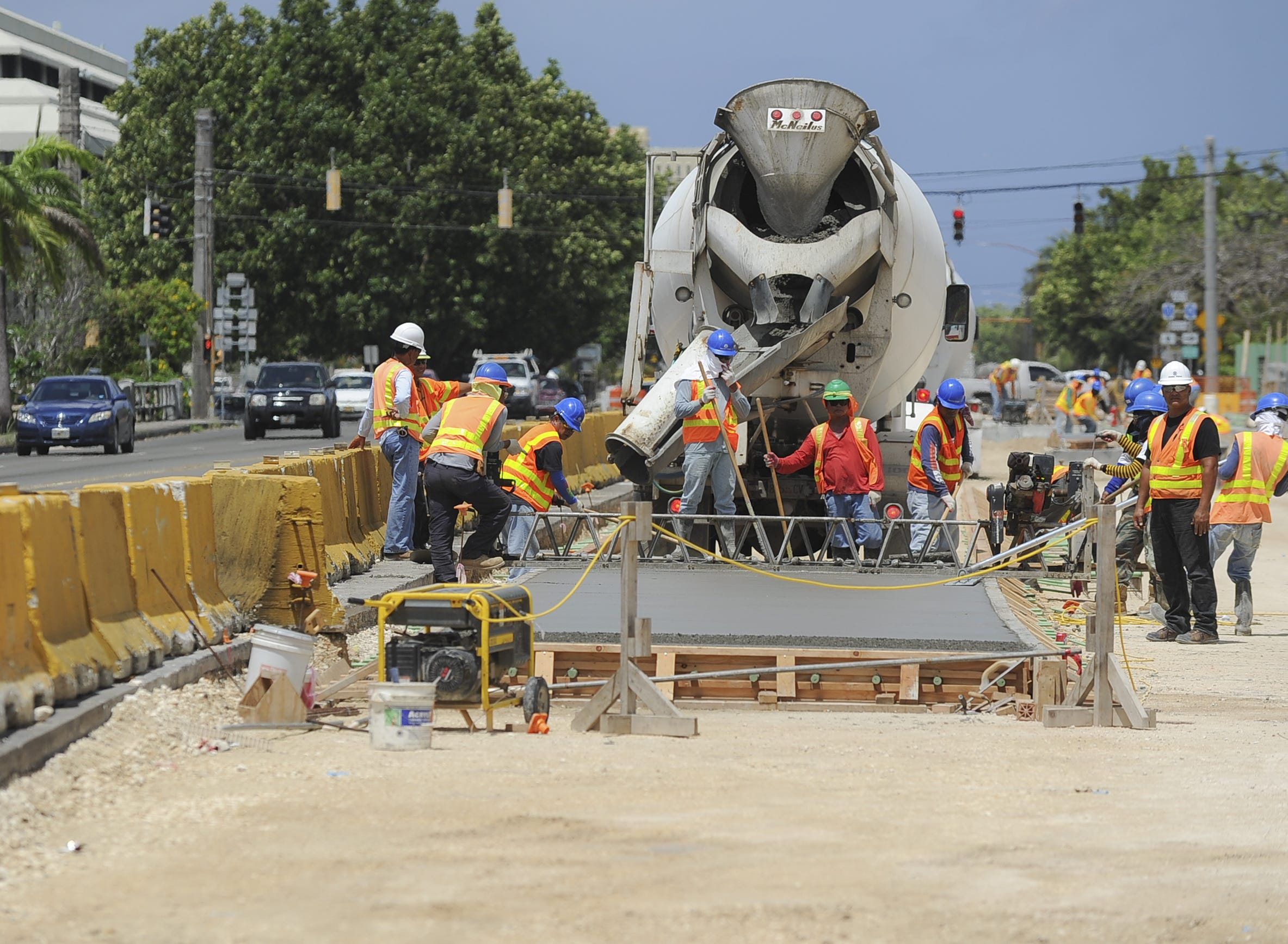 In this April 2013 file photo, Core Tech International employees install a section of rigid pavement on Marine Corps Drive as part of the bridge replacement project. The project, entirely funded by the military, is in connection with the pending military buildup. The Department of Public Works has accused Core Tech of improper delays in completing the project.
